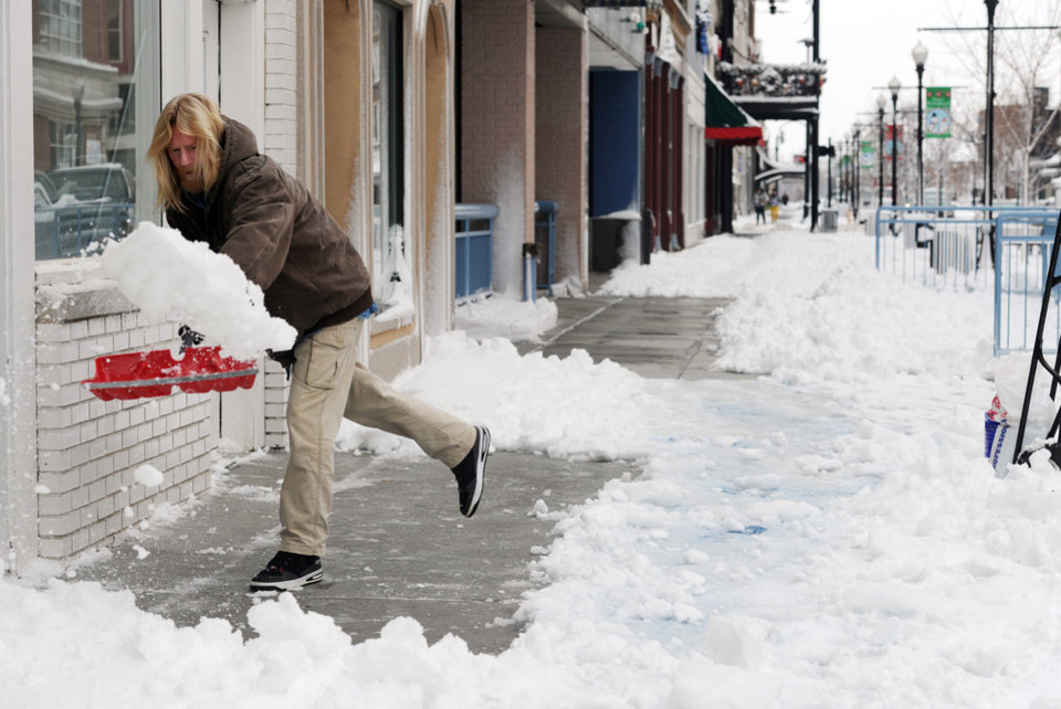 Scott Becker shovels the sidewalks of businesses along Main Street in downtown Evansville, Ind., on Thursday morning, Dec. 27, 2012. (AP Photo/The Evansville Courier & Press, Erin McCracken)