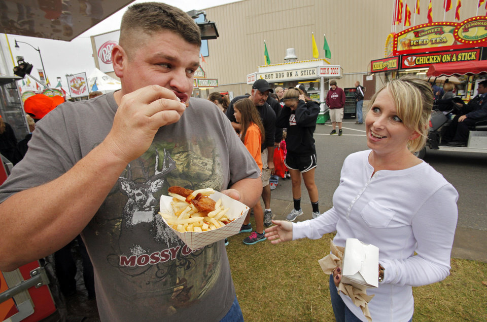 Photo - Patrick Jarrels, Lindsay, samples batter fried bacon as Billea Taylor watches during the 106th Oklahoma State Fair at State Fair Park on Saturday, Sept. 15, 2012, in Oklahoma City, Okla.  Photo by Steve Sisney, The Oklahoman