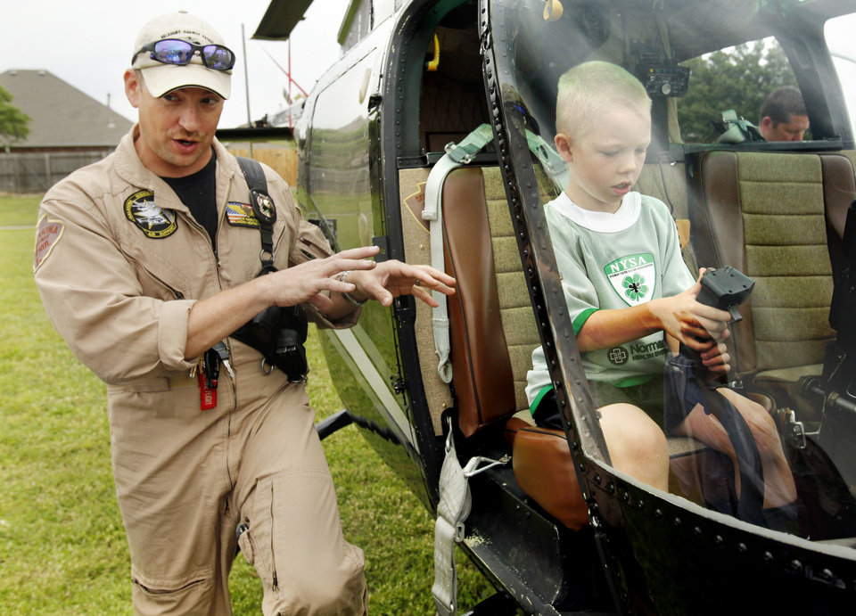 Helicopter pilot Drew Hamilton with the Oklahoma Highway Patrol explains the use of the helicopter to parents while Gabriel Inman, 8, sits at the controls.