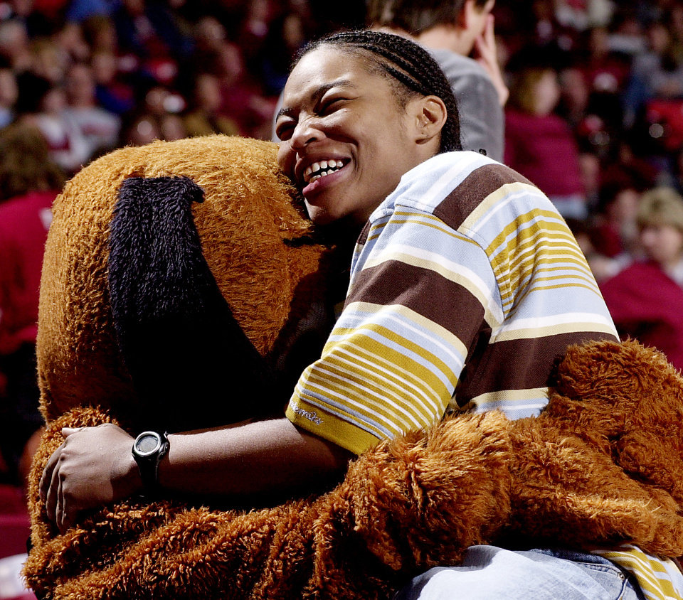 MASCOT: Former University of Oklahoma women's college basketball player Rosalind Ross gets a hug from Top Daug during the OU-Texas game this past week. Ross is now a WNBA player. Oklahoman staff Photo by Ty Russell.