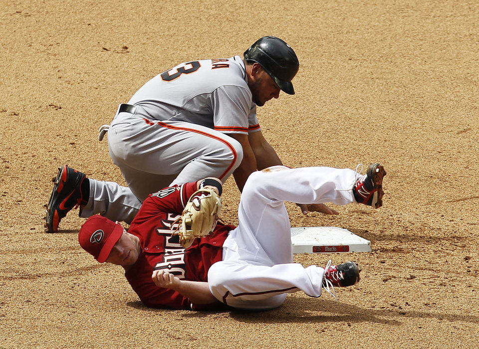 Photo -   Arizona Diamondbacks' Aaron Hill, front, takes a tumble after falling over San Francisco Giants' Melky Cabrera, who dives back safely into second base during the sixth inning in an MLB baseball game Sunday, April 8, 2012, in Phoenix.(AP Photo/Ross D. Franklin)