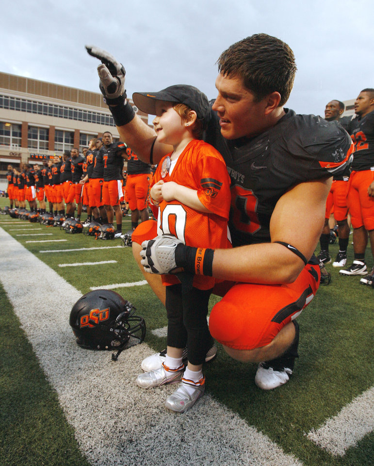 Cancer patient Taylor Brandt, 5, joins Oklahoma State's Cooper Bassett (80) in celebration and singing the school song after the  college football game where the Oklahoma State University Cowboys (OSU) defeated the University of Kansas Jayhawks (KU) 70-28 at Boone Pickens Stadium in Stillwater, Okla., Saturday, Oct. 8, 2011 Photo by Steve Sisney, The Oklahoman