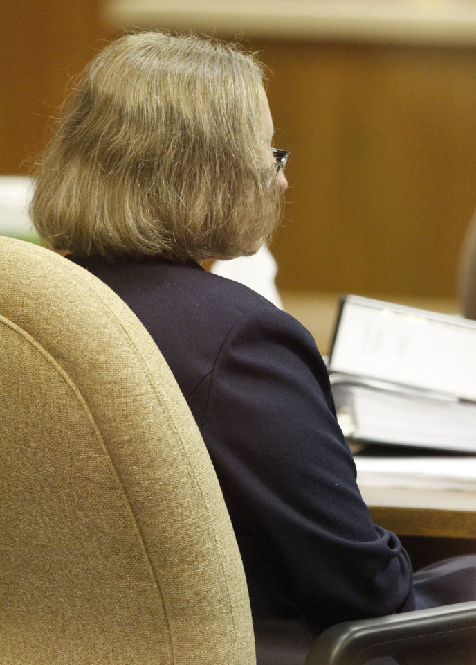 Photo - Rebecca Bryan listens to Gary James, defense attorney for give closing arguments in the Canadian County Courthouse in El Reno , Tuesday May 21, 2013. Bryan is accused of killing her husband, Keith Bryan, 52, who was the Nichols Hills fire Chief. Photo By Steve Gooch, The Oklahoman