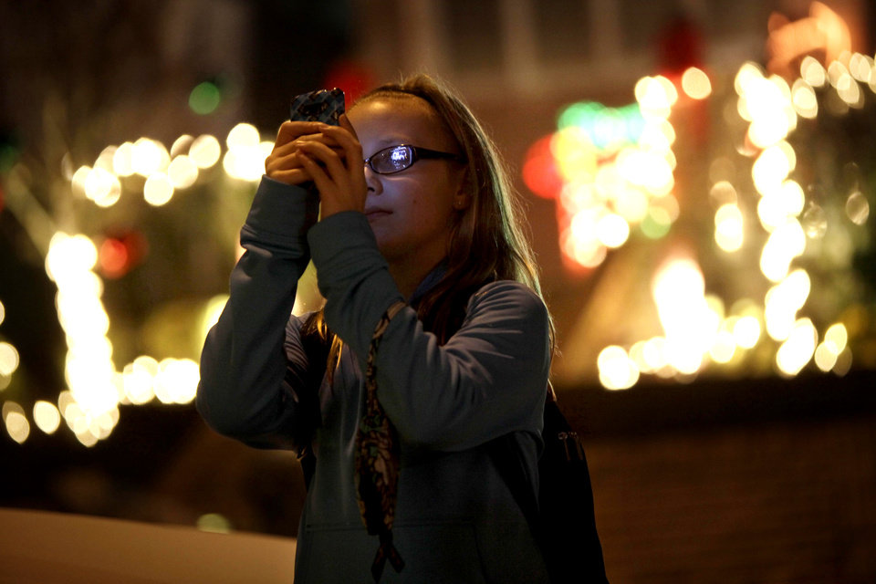 "This Dec. 4, 2012 photo shows Lyvia Markle, 11, of Rochester, N.Y., taking photos of holiday displays in the Brooklyn borough of New York. Each holiday season, tour operator Muia takes tourists from around the world on his ""Christmas Lights & Cannoli Tour"" visiting the Brooklyn neighborhoods of Dyker Heights and Bay Ridge, where locals take pride in over-the-top holiday light displays.  (AP Photo/Seth Wenig)"