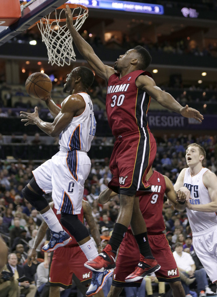Charlotte Bobcats' Kemba Walker, left, drives past Miami Heat's Norris Cole (30) during the first half of an NBA basketball game in Charlotte, N.C., Saturday, Jan. 18, 2014. (AP Photo/Chuck Burton)