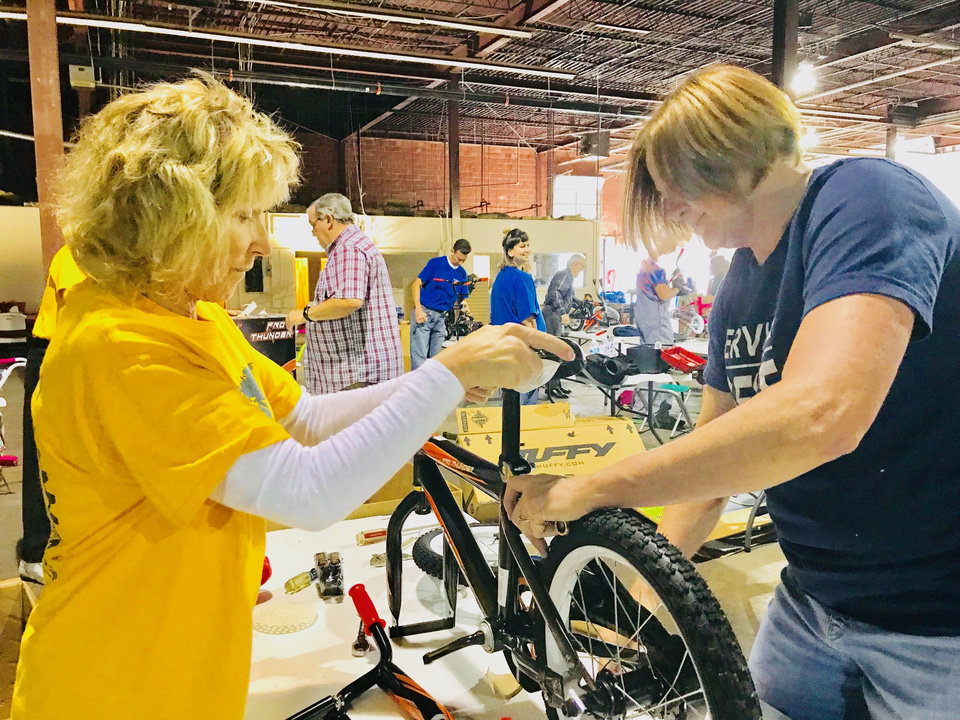 Photo -  OKC Sunshine Rotary Club member Lisa Baker, of Oklahoma City, works on a bicycle with fellow Rotary Club member Roxy Butler, of Bethany, at The Salvation Army's 2017