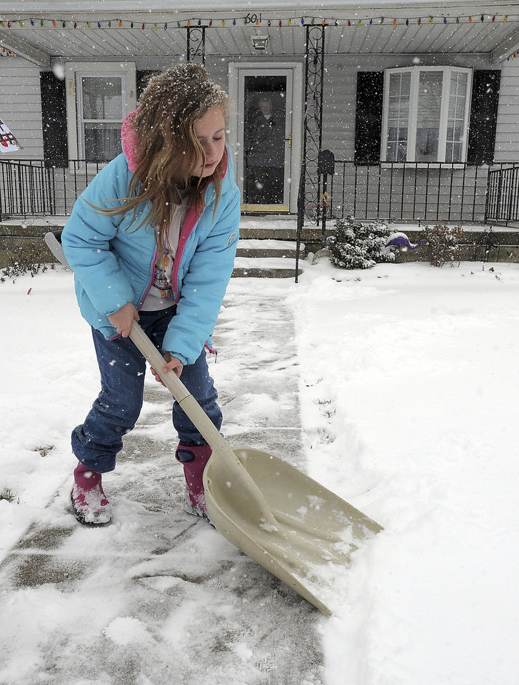 Photo - Ava Krasauskis, 8, helps her grandmother by shoveling the front walk of her grandmother's Brooklyn Park home, Tuesday, Jan. 21, 2014, in Brooklynn Park, Md. A heavy snow falls in northern Anne Arundel County Tuesday afternoon. (AP Photo/Capital Gazette, Paul W. Gillespie)