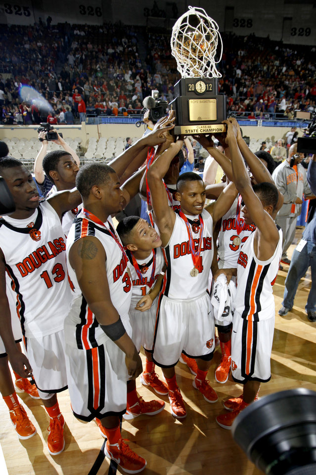 Photo - CLASS 4A HIGH SCHOOL BASKETBALL / STATE TOURNAMENT: The Douglass team lifts the trophy after their 86-53 win over Anadarko in the Class 4A boys high school state basketball championship game at State Fair Arena in Oklahoma City, Saturday, March 10, 2012. Photo by Bryan Terry, The Oklahoman