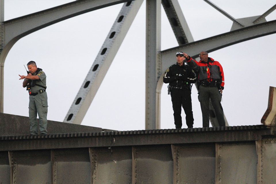 Photo - Rescue workers look over the edge where a portion of the Interstate 5 bridge collapsed into the Skagit River in Mount Vernon, Wash., Thursday, May 23, 2013. (AP Photo/Joe Nicholson)