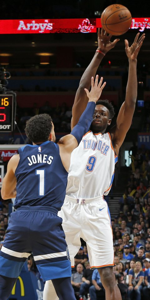 Photo - Oklahoma City's Jerami Grant (9) passes over Minnesota's Tyus Jones (1) during an NBA basketball game between the Oklahoma City Thunder and the Minnesota Timberwolves at Chesapeake Energy Arena in Oklahoma City, Sunday, Oct. 22, 2017. Photo by Nate Billings, The Oklahoman