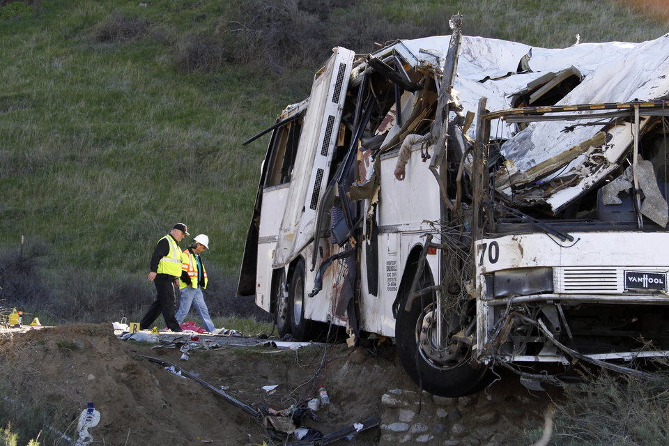 Photo - Authorities continue their investigation of the scene where at least eight people were killed and at least 38 people were injured after a tour bus carrying a group from Tijuana, Mexico crashed with two other vehicles just north of Yucaipa, Calif., Sunday, Feb. 3, 2013. (AP Photo/Reed Saxon)