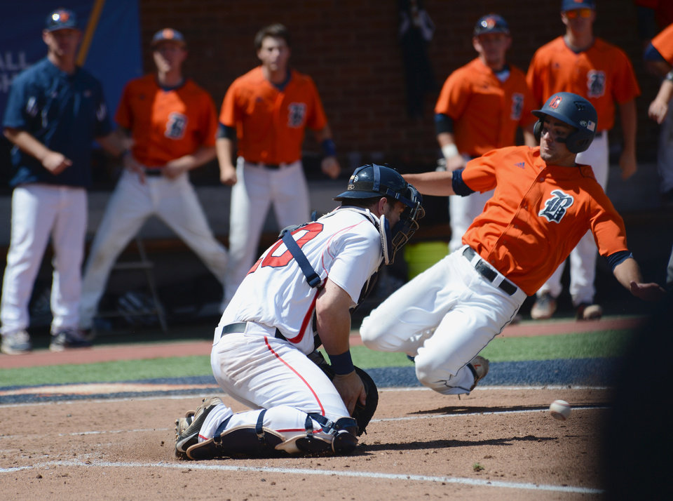 Photo - Bucknell's Anthony Gingerelli slides in just ahead of the throw to Liberty catcher Danny Grauer, on a hit by teammate Jon Mayer during the second inning of an NCAA college baseball regional tournament game in Charlottesville, Va., Saturday, May 31, 2014. (AP Photo/Pat Jarrett)