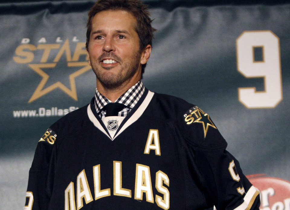 Photo - FILE - In this Sept. 23, 2011, file photo, NHL hockey player Mike Modano wears a Dallas Stars jersey during a news conference announcing his retirement in Dallas. Modano had several tearful farewells as his playing days wound down. The guy who made hockey cool in Dallas figures he'll get emotional again for the final ceremony: retiring his iconic No. 9 during the Stars' game against Minnesota on Saturday, March 8. (AP Photo/LM Otero, File)