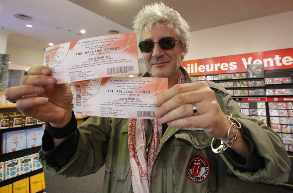 Photo -   Rolling Stones fan who named himself Patrice, 55, and who claims he has seen 54 Rolling Stones concerts, shows the tickets he bought for Thursday night's concert in Paris, Thursday, Oct. 25, 2012. The Rolling Stones announced a surprise