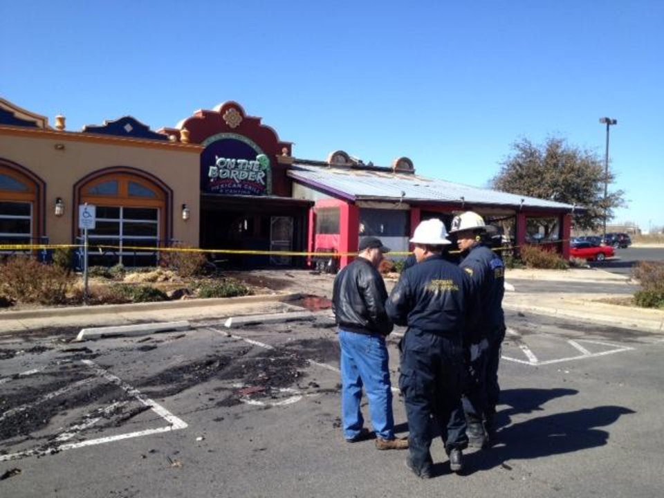 Photo -  Norman fire officials talk outside the On The Border restaurant, which was destroyed by fire early Saturday morning. Photo by Steve Sisney, The Oklahoman