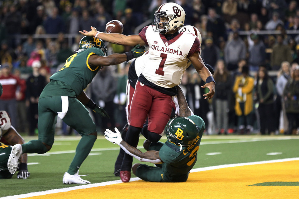 Photo - Oklahoma quarterback Jalen Hurts (1) fumbles the ball while getting tackled by Baylor safeties Henry Black (8) and Chris Miller (3) during an NCAA college football game, Saturday, Nov. 16, 2019, in Waco, Texas. Oklahoma won 34-31. (Ian Maule/Tulsa World via AP)