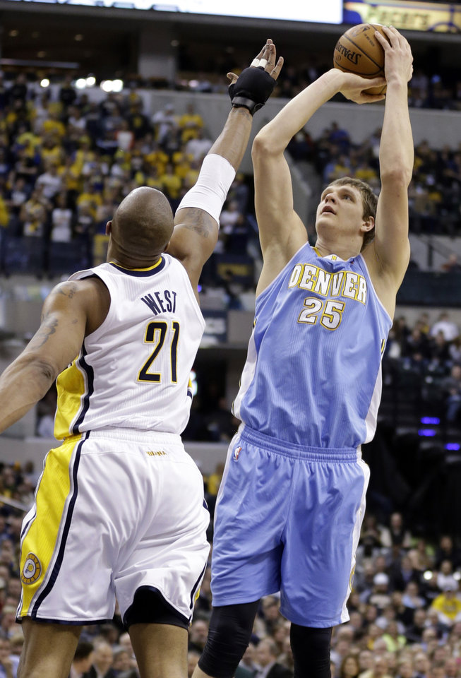 Photo - Denver Nuggets center Timofey Mozgov (25) shoots over Indiana Pacers forward David West in the first half of an NBA basketball game in Indianapolis, Monday, Feb. 10, 2014. (AP Photo/Michael Conroy)