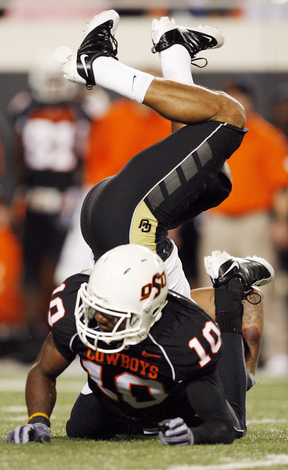 Photo - Markques Simas (6) of Colorado flips over after being stopped by OSU's Markelle Martin (10) in the first quarter during the college football game between Oklahoma State University (OSU) and the University of Colorado (CU) at Boone Pickens Stadium in Stillwater, Okla., Thursday, Nov. 19, 2009. Photo by Nate Billings, The Oklahoman