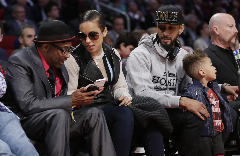 Spike Lee, left, talks with singer Alicia Keys as her husband Swizz Beatz and their son Egypt sit courtside during NBA All-Star Saturday Night basketball in Houston on Saturday, Feb. 16, 2013. (AP Photo/Eric Gay)