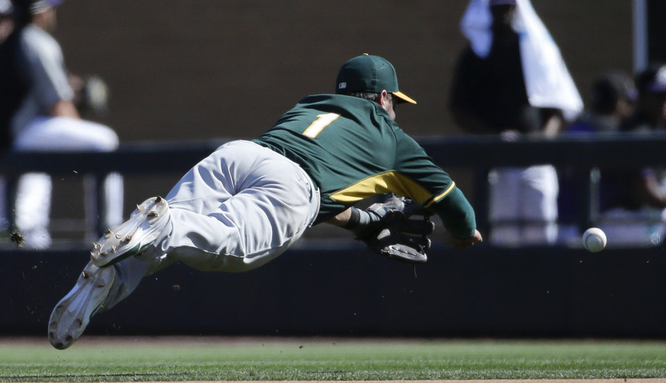 Photo - Oakland Athletics first baseman Nick Punto can't get a glove on a hit by Colorado Rockies' Jason Pridie during the third inning of a spring training baseball game in Scottsdale, Ariz., Saturday, March 8, 2014. (AP Photo/Chris Carlson)