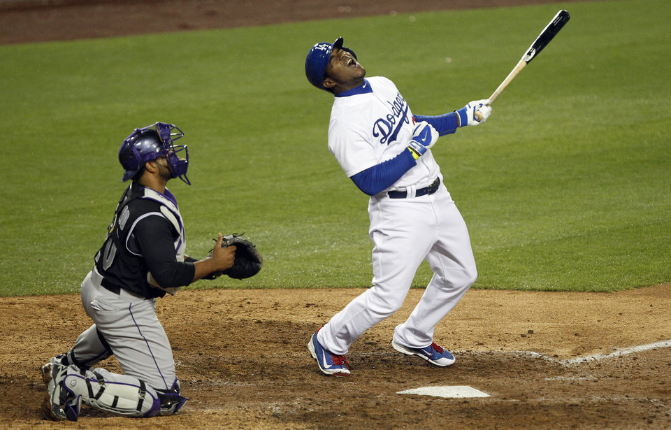 Photo - Los Angeles Dodgers' Yasiel Puig, right, reacts to hitting a fly ball for an out to right field with Colorado Rockies catcher Wilin Rosario, left, looking on in the eighth inning of a baseball game on Friday, April 25, 2014, in Los Angeles. (AP Photo/Alex Gallardo)