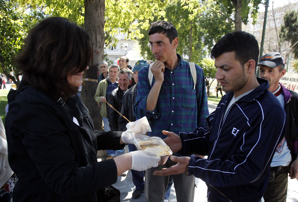 Photo -   A volunteer distributes free meals during a soup kitchen organized by a Greek humanitarian group in Athens' main Syntagma square on Sunday, April 1 2012. Greece's austerity cutbacks have deepened the economic recession, and torn holes in the country's social fabric. Unemployment has hit a record high of 21 percent, and thousands of Greeks depend on church and municipal soup kitchens for sustenance. (AP Photo/Kostas Tsironis)