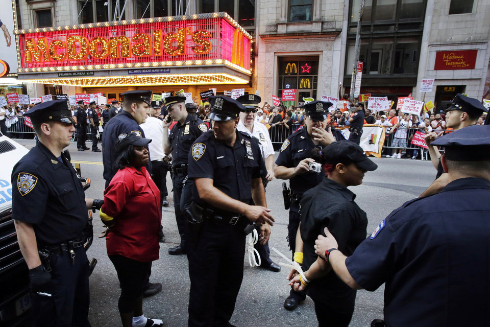 Photo - Police officers arrest two protesters in front of a McDonald's restaurant on 42nd Street in New York's Times Square as police officers move in to begin making arrests, Thursday, Sept. 4, 2014. The protesters are seeking to get pay increases to $15 per hour. Thursday's demonstration is part of a day of planned protests in 150 cities across the country by workers from fast-food chains. (AP Photo/Mark Lennihan)