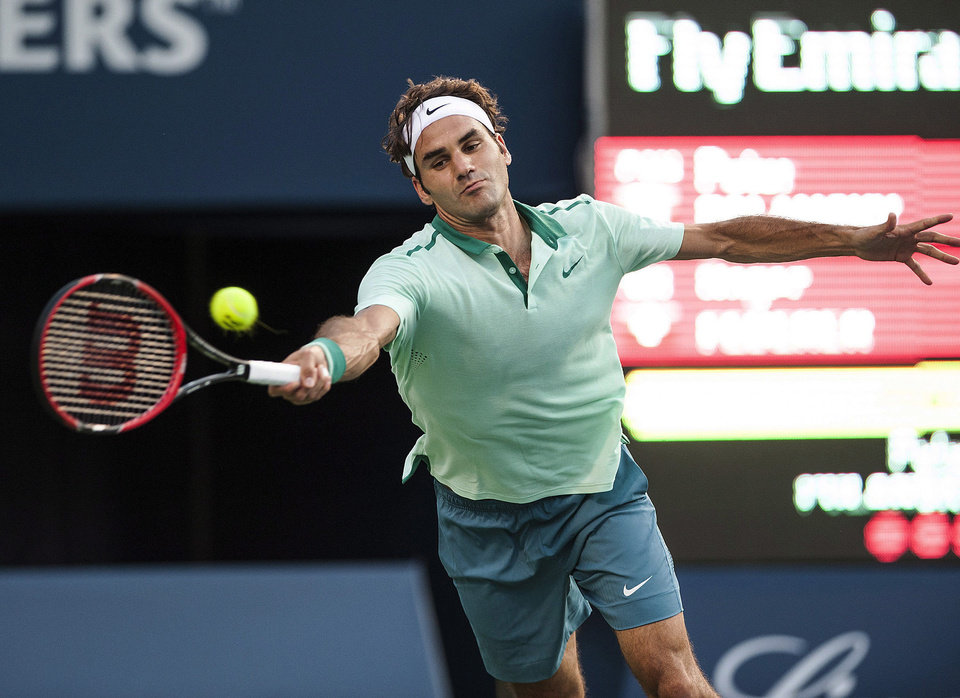 Photo - Roger Federer, of Switzerland, reaches for a shot from Canada's Peter Polansky during the Rogers Cup men's tennis tournament in Toronto on Tuesday, Aug. 5, 2014. (AP Photo/The Canadian Press, Aaron Vincent Elkaim)