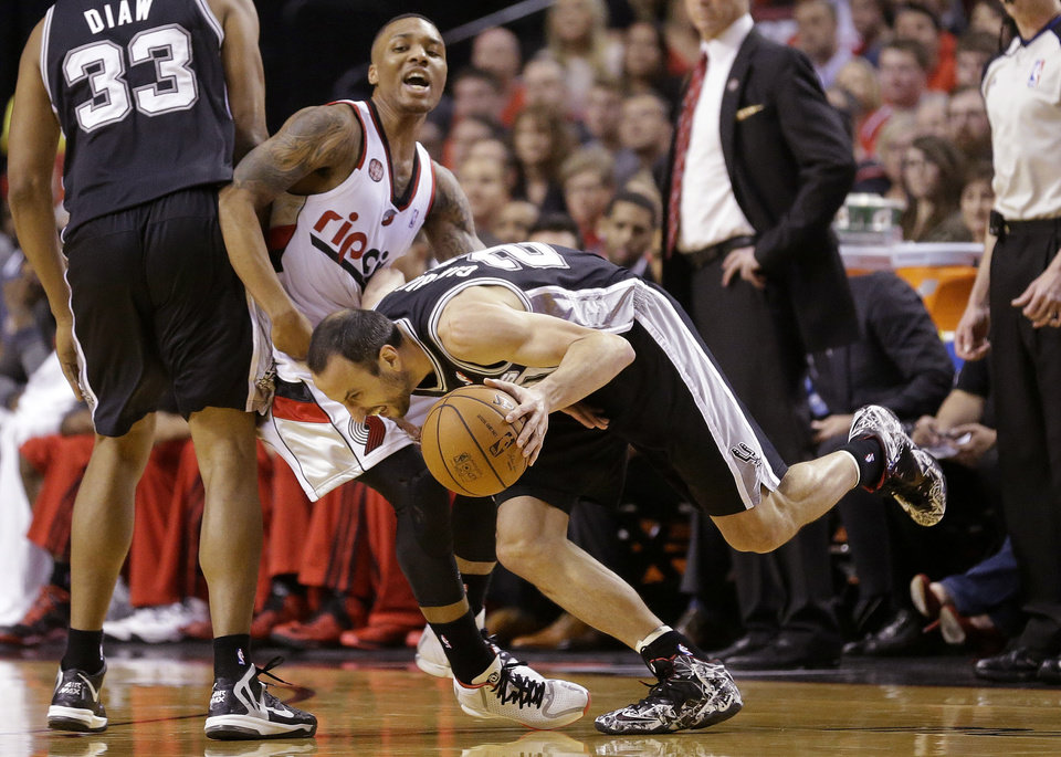 Photo - Portland Trail Blazers' Damian Lillard, center, guards San Antonio Spurs' Manu Ginobili, foreground, in the first quarter during Game 4 of a Western Conference semifinal NBA basketball playoff series Monday, May 12, 2014, in Portland, Ore. (AP Photo/Rick Bowmer)