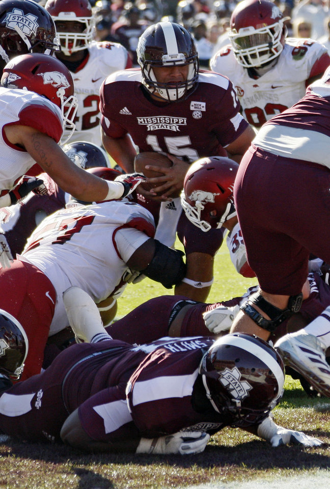 Photo -   Mississippi State quarterback Dak Prescott (15) pushes through Arkansas defenders for a touchdown in the third quarter of an NCAA college football game in Starkville, Miss., Saturday, Nov. 17, 2012. Mississippi State won 45-14. (AP Photo/Rogelio V. Solis)