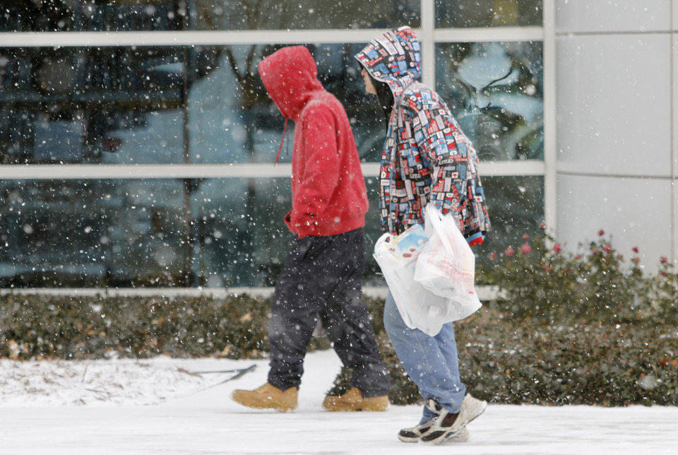 Photo -  Pedestrians walk on Park Avenue as snow moves into the downtown area of Oklahoma City, Thursday December 5, 2013. Photo By Steve Gooch, The Oklahoman
