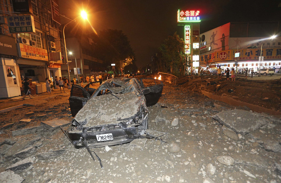 Photo - A crushed vehicle sits in rubble on a destroyed street after multiple explosions from an underground gas leak in Kaohsiung, Taiwan, early Friday, Aug. 1, 2014. A massive gas leakage early Friday caused five explosions that killed several people and injured over 200 in the southern Taiwan port city of Kaohsiung. (AP Photo)  TAIWAN OUT
