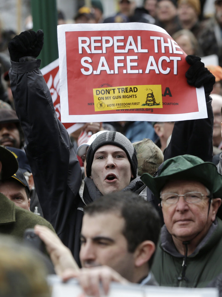 Photo - A gun rights advocates holds a sign during a demonstration outside the Capitol on Thursday, Feb. 28, 2013, in Albany, N.Y. The group rallied against the recently legislated NY SAFE Act and other measures they say infringe on their constitutional right to bear arms. (AP Photo/Mike Groll)