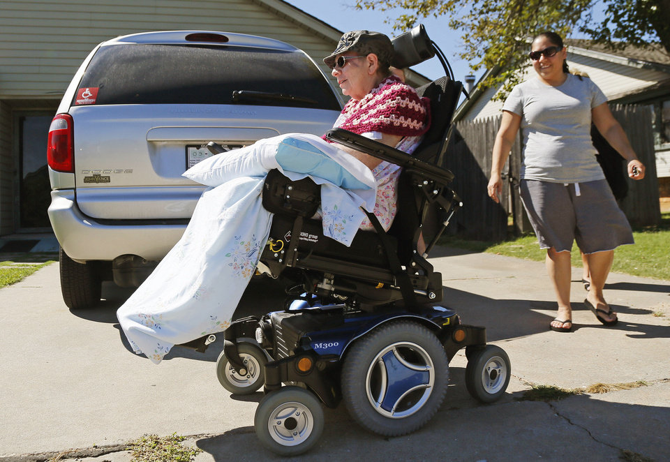 Photo - Edith Morales rolls past her new wheelchair-accessible van as her daughter, Christina Morales, watches.  PHOTO BY NATE BILLINGS, THE OKLAHOMAN.  NATE BILLINGS