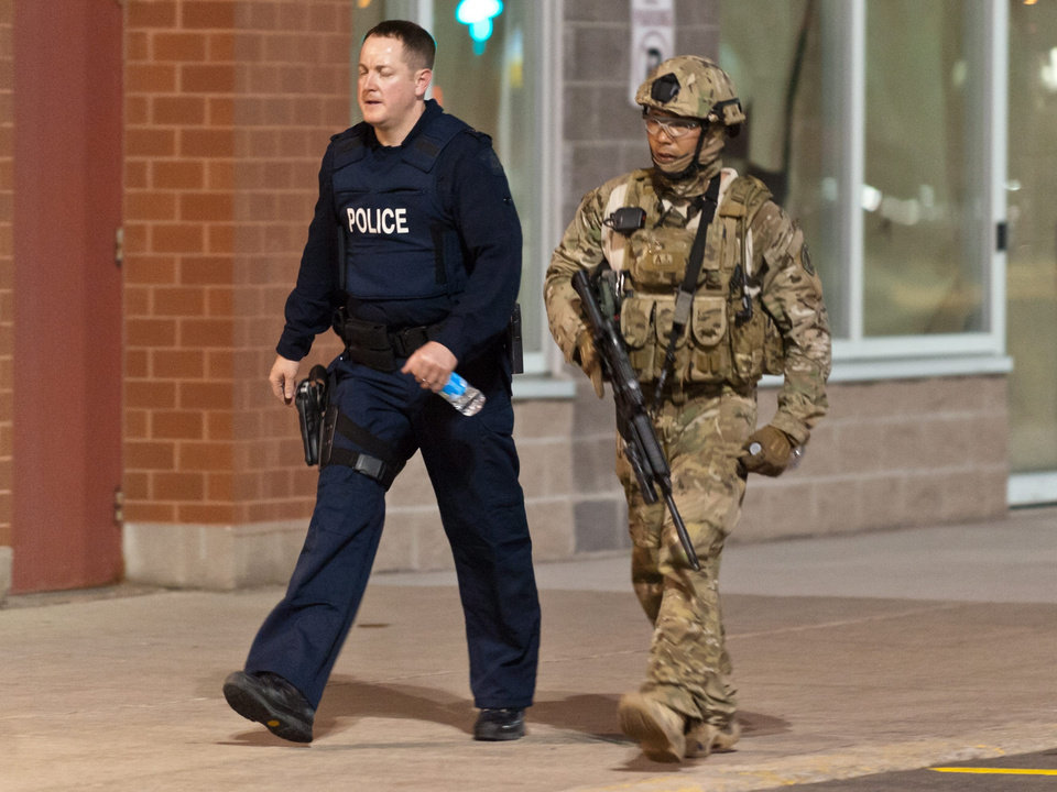 Photo - Police officers walk around a strip mall urging merchants to shut down their stores in Moncton, New Brunswick, on Wednesday, June 4, 2014. Police New Brunswick were searching Wednesday for an armed man after at least two people, both police officers, were injured in a shooting. The Royal Canadian Mounted Police in New Brunswick said on its Twitter feed that they were looking for 24-year-old Justin Bourque of Moncton, who is considered armed and dangerous. The police force tweeted an image of a suspect wearing military camouflage and wielding two guns. (AP Photo/The Canadian Press, Marc Grandmaison)