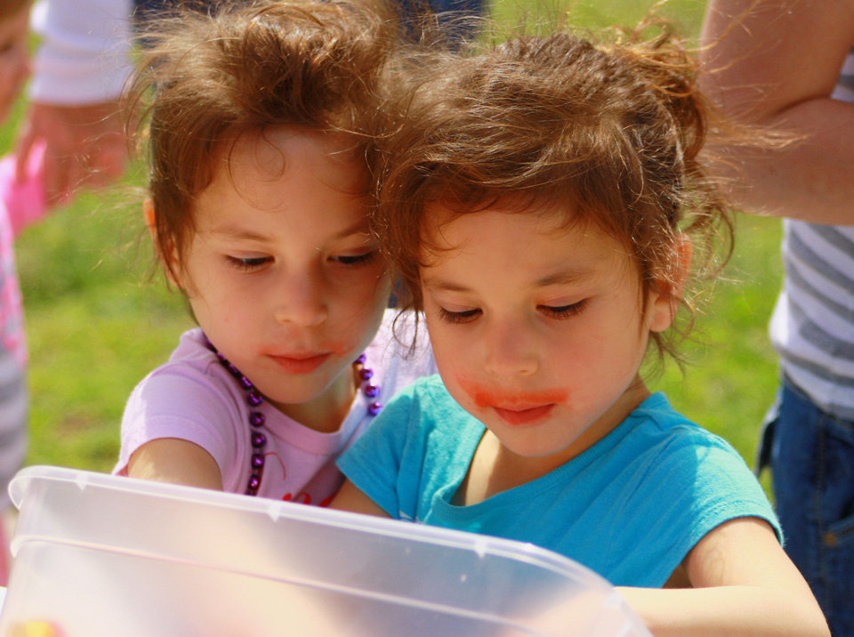 Photo - Twin sisters Kyran, left, and Kirsten Perez, 5, take a close look at treats offered to participants Saturday at