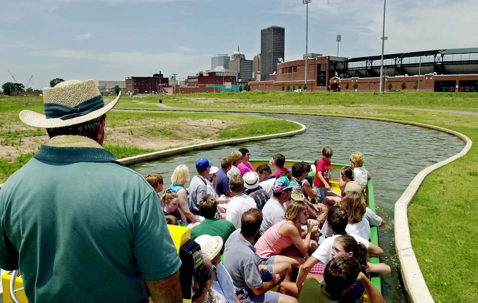 Photo - Less Ford pilots his water taxi boat on the south end of the Bricktown canal on the eve of the first anniversary of the canal opening.