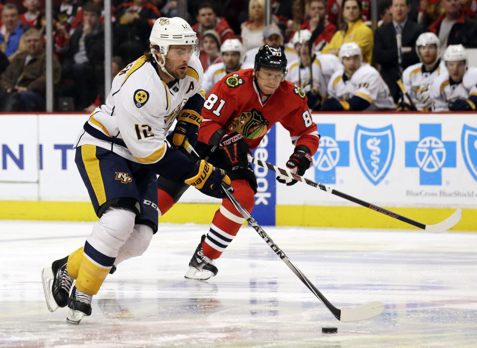 Photo - Nashville Predators' Mike Fisher (12), left, controls the puck past Chicago Blackhawks ' Marian Hossa (81) during the first period of an NHL hockey game in Chicago, Sunday, March 23, 2014. (AP Photo/Nam Y. Huh)