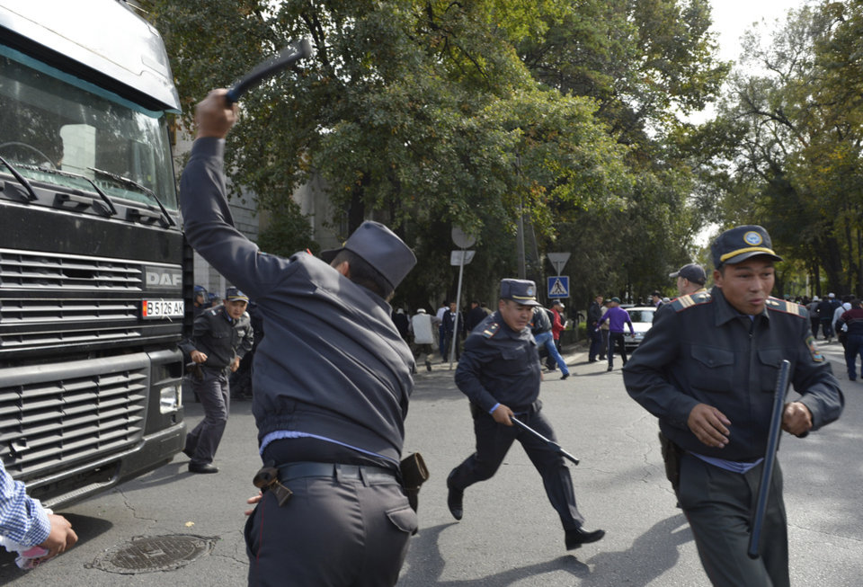 Photo -   Police officers try to stop a truck carrying protesters in downtown Bishkek, Kyrgyz capital on Wednesday, Oct. 3, 2012. Around 1,000 people gathered in the center of the city for a rally, organized by nationalist politicians Sapar Zhaparov and Kamchibek Tashiyev, ostensibly to demand the nationalization of a controversial gold mine in the east of the Central Asian nation. Police officers protecting the government building, known as the White House, used dogs and smoke bombs to disperse a group of young men who attempted to scale the gates. (AP Photo/ Vladimir Voronin)