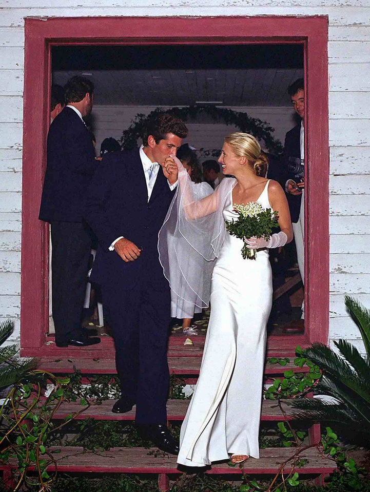 Photo - FILE-   This Sept. 21, 1996 file photo shows John F. Kennedy Jr., the son of President John F. Kennedy, and Carolyn Bessette as they leave a church after being wed in a small private ceremony on Cumberland Island, off the coast of Georgia. The extravagance of the mid-'80s largely went out with the stock-market crash in 1987, and wedding gowns started down a path toward simpler and chicer.   (AP Photo/Copyright 1996, Denis Reggie, FILE)