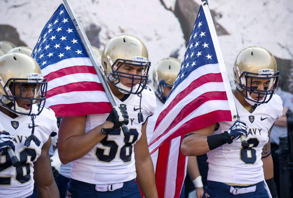 Photo - FILE - In this Sept. 7, 2013, file photo, from left, Navy's Marcus Thomas (26), Evan Palelei (58) and Wave Ryder (8) head onto the field at the start of an NCAA college football game against Indiana in Bloomington, Ind. The Defense Department said Tuesday, Oct. 1, 2013, that it has temporarily suspended all sports competitions at the service academies as a result of the partial government shutdown. The decision jeopardizes this weekend's football games , Air Force at Navy and Army at Boston College. (AP Photo/Doug McSchooler, File)
