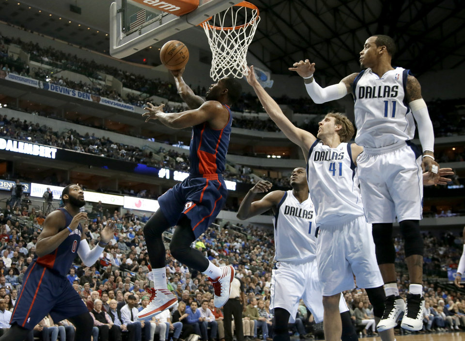 Photo - Detroit Pistons' Rodney Stuckey (3) goes up for a shot after getting by Dallas Mavericks' Samuel Dalembert (1) of Haiti, Dirk Nowitzki (41), of Germany, and Monta Ellis (11) in the first half of an NBA basketball game, Sunday, Jan. 26, 2014, in Dallas. (AP Photo/Tony Gutierrez)