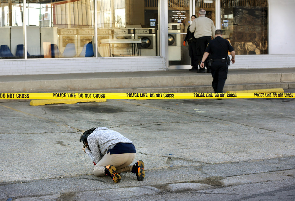 Photo -  A woman collapses in grief in front of the Laundry Station, the scene of a double killing in Del City. She believed one of the victims was her mother. Police have not released the identities of the victims.[Photo by Jim Beckel, The Oklahoman]