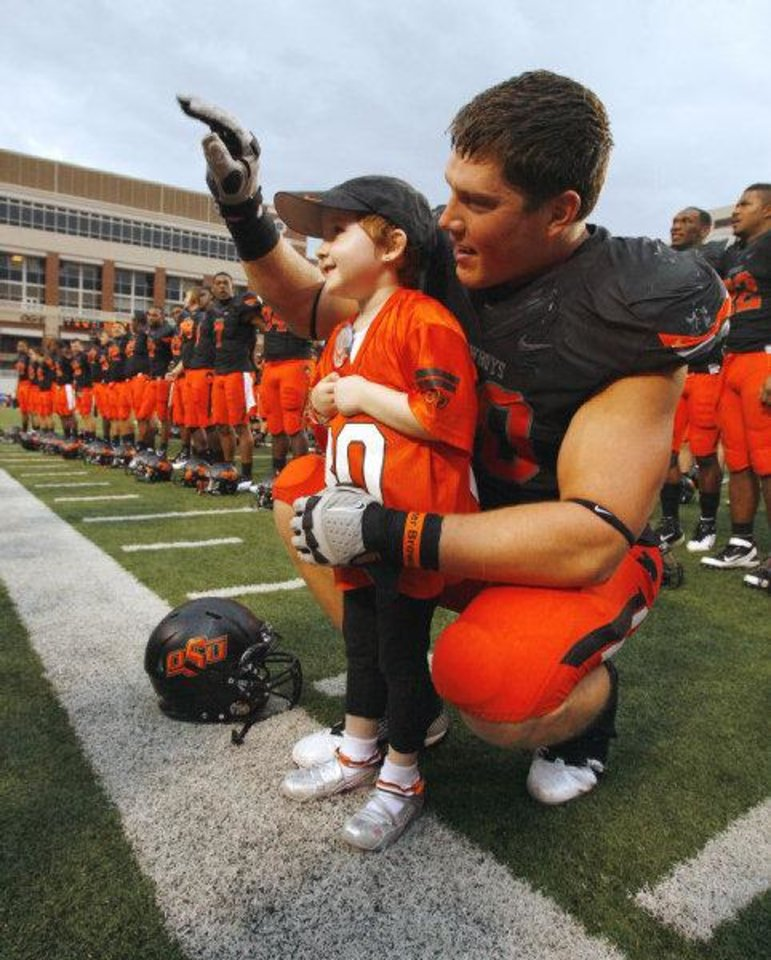 Photo - Taylor Brandt, 5, joins Oklahoma State's Cooper Bassett in celebration and singing the school song after the Cowboys' 70-28 win over Kansas on Oct. 8. Photo by Steve Sisney, The Oklahoman