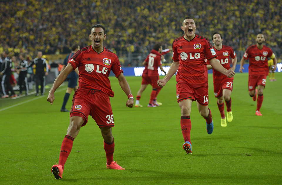 Photo - Leverkusen's Karim Bellarabi, left, celebrates during the German Bundesliga soccer match between Borussia Dortmund and Bayer Leverkusen in Dortmund,  Germany, Saturday, Aug. 23, 2014. Borussia was defeated by Bayer with 0-2. (AP Photo/Martin Meissner)