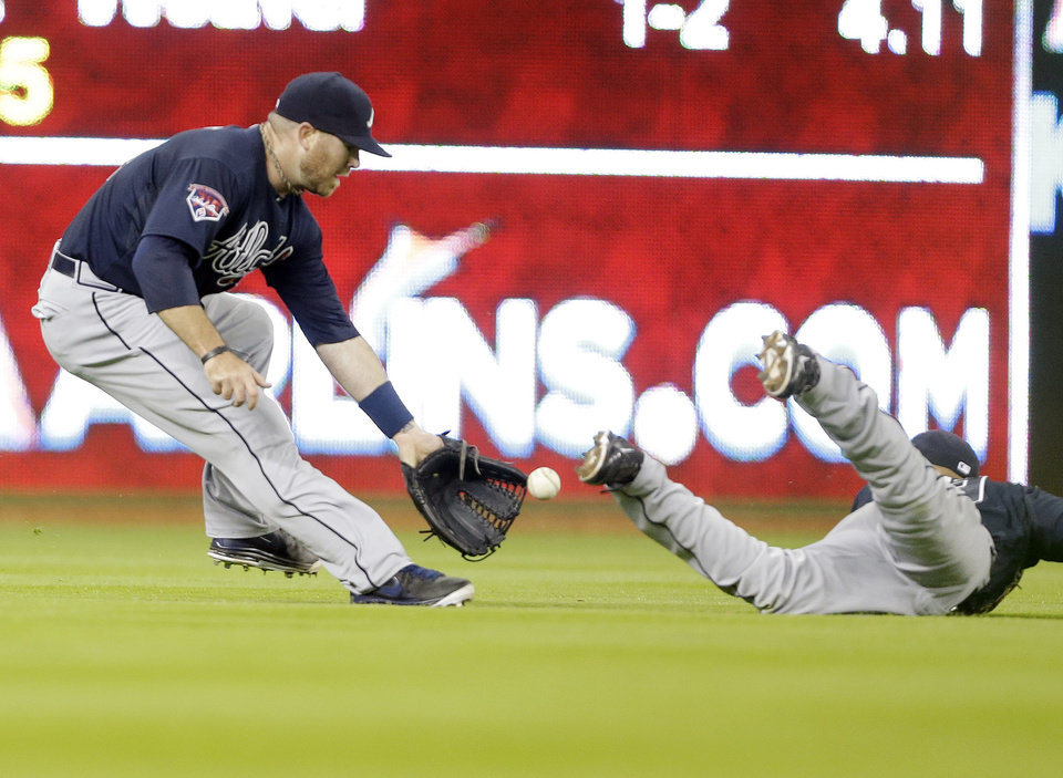 Photo - Atlanta Braves left fielder Ryan Doumit, left, and Atlanta Braves' short stop Andrelton Simmons, right, can't come up with a single hit by Miami Marlins' Jarrod Saltalamacchia during the fourth inning of a baseball game, Tuesday, April 29, 2014, in Miami. (AP Photo)