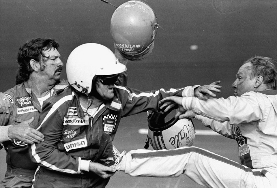 FILE - In this Feb. 18, 1979 file photo, Bobby Allison holds race driver Cale Yarborough\'s foot after Yarborough kicked him following an incident on the final lap final lap of the Daytona 500 in Daytona Beach, Fla. NASCAR added a rule Friday, Aug. 15, 2014, ordering drivers to not approach the track or moving cars after accidents.