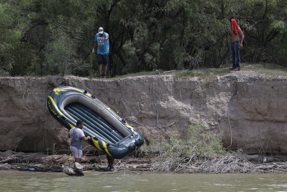 Photo - Unidentified men pull a raft to shore on the Mexico side of the Rio Grand, Thursday, July 24, 2014, in Mission, Texas. Texas is spending $1.3 million a week for a bigger DPS presence along the border. (AP Photo/Eric Gay, Pool)