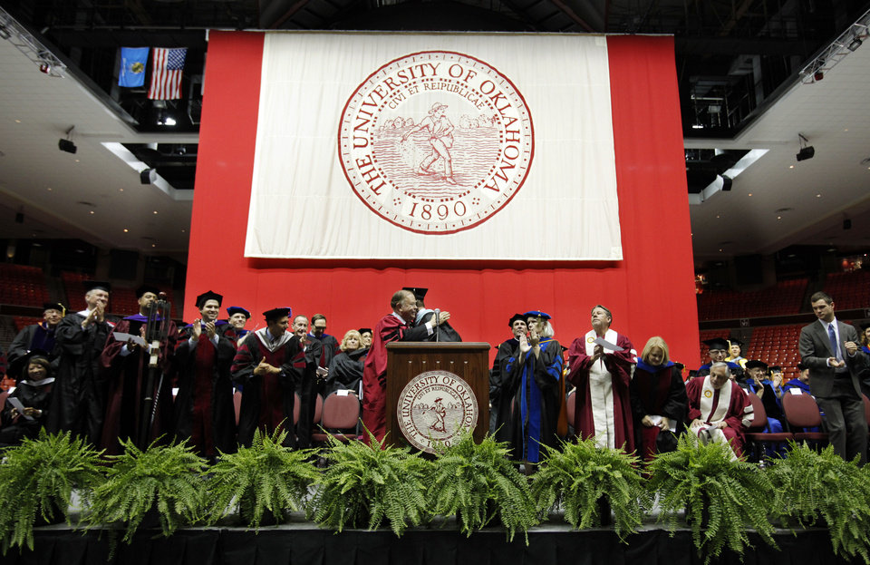 Photo - University of Oklahoma president David Boren hugs presenter Clark Stroud after his introduction, and the faculty gives a standing ovation to the president during the 2012 Convocation Ceremony at the Lloyd Noble Center on Thursday in Norman.     Photo by Steve Sisney, The Oklahoman  STEVE SISNEY - THE OKLAHOMAN