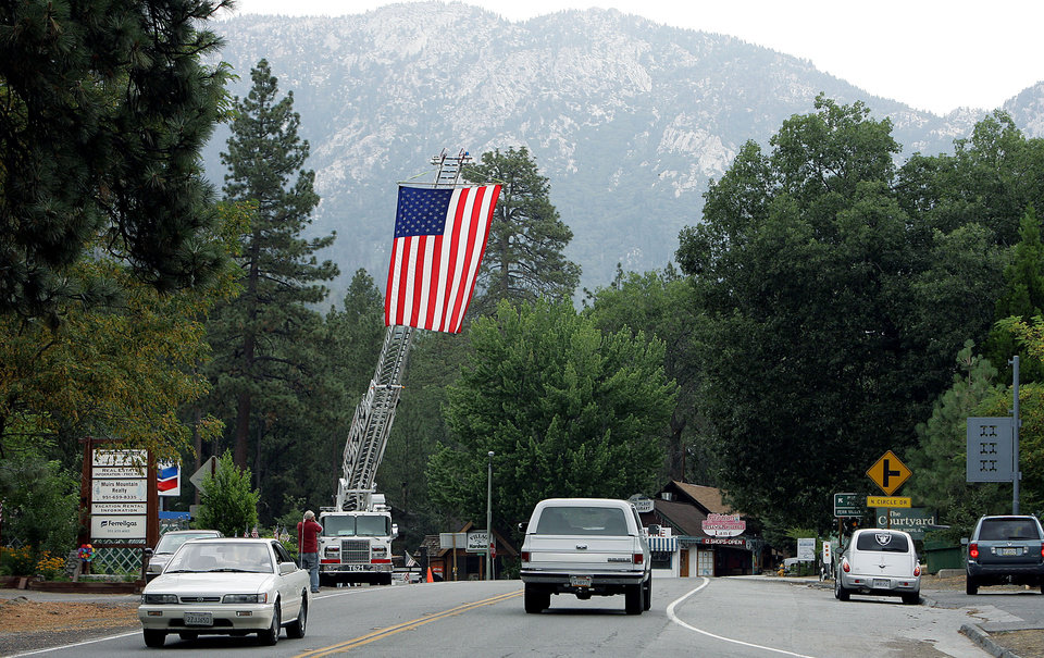 Photo - A ladder truck flies the American flag to greet residents back to Idyllwild after the evacuation order was rescinded Sunday, July 21, 2013, in the areas affected by the Mountain Fire. Thousands of people were allowed to return to their homes in Southern California mountain communities near Palm Springs on Sunday, after firefighters aided by heavy rain made substantial progress against a week-old wildfire that has burned across 42 square miles and destroyed seven homes. (AP Photo/The Press-Enterprise, Terry Pierson)